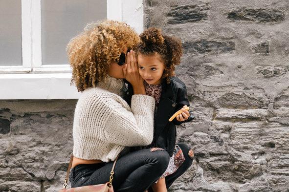 mère qui chuchote à l'oreille de sa fille